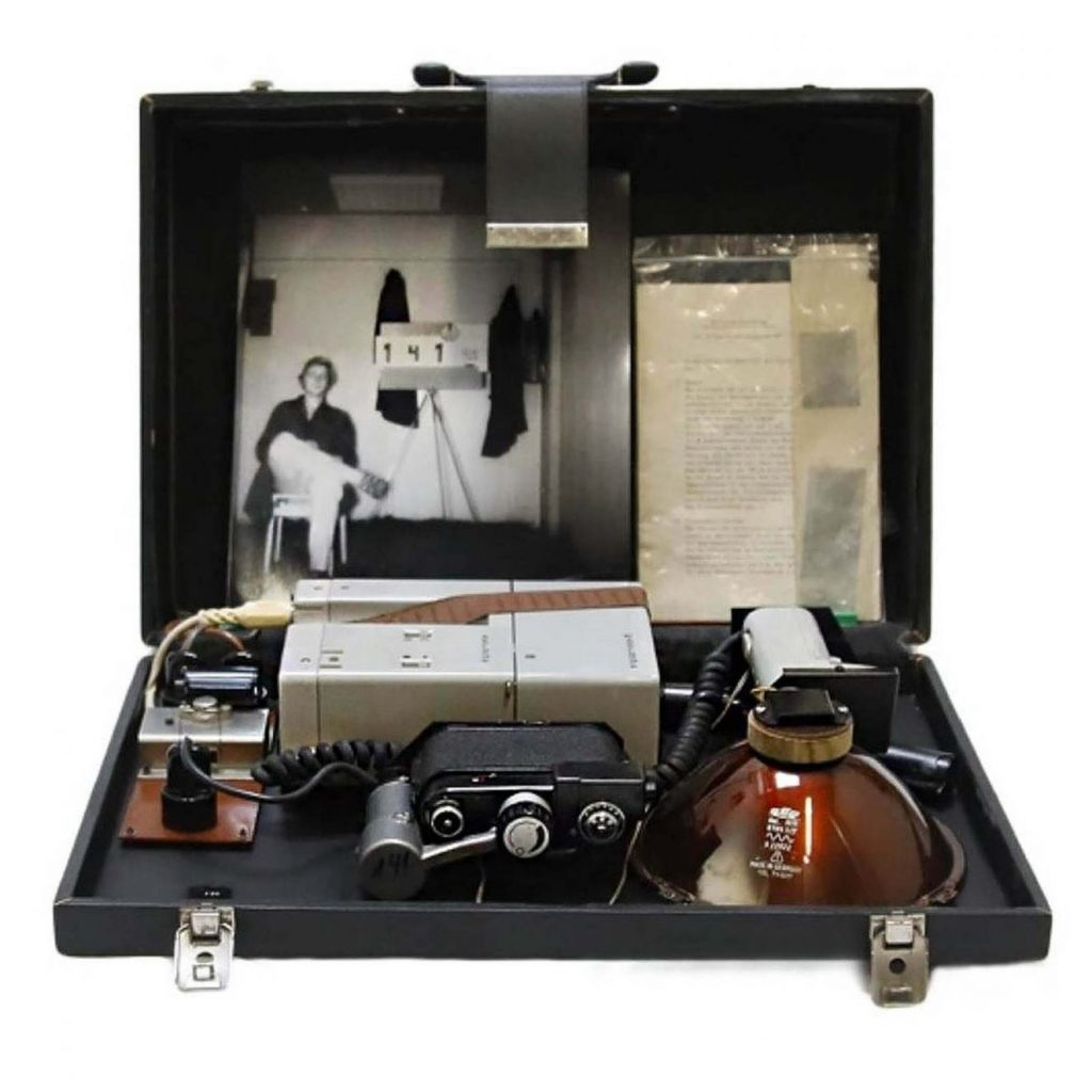 Suitcase of the STASI (secret service of the GDR) equipped with a special camera and an invisible infrared illuminator for clandestine photography, circa 1970. This system allows the taking of photographs at night or in foggy weather. The photograph, taken in total darkness, shows a STASI technician testing this equipment (suitcase numbered 141). © Marché Dauphine - Photo Sixtine Legrand