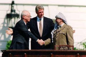 Historic handshake at the signing of the Oslo Accords on the White House lawn, September 13, 1993: encouraged by Bill Clinton, Yasser Arafat extends his hand to Yitzhak Rabin, who takes it after a brief hesitation (Wikipedia)